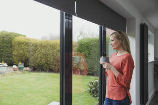 lady-looking-out-of-bi-fold-doors-on-to-garden